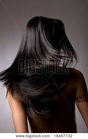 Beautiful dark hair from behind on grey background
