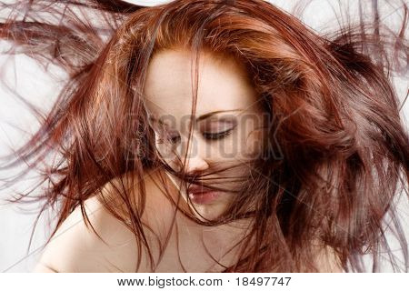 Face shot of redhead woman with hair billowing around everywhere