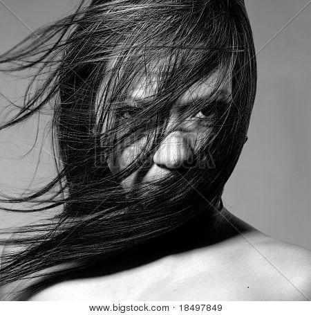Modelo de belleza desnuda en estudio con pelo soplado por el viento