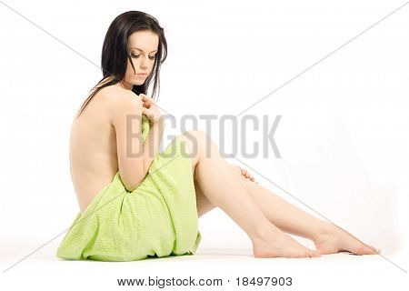 Nude beauty sits with towel on white background