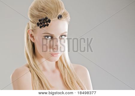 Head and shoulders of blonde fashon model on grey studio background