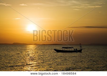 Sun setting over ocean with Asian fishing  boat