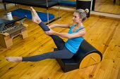 Fit woman doing pilates on arc barrel in fitness studio poster