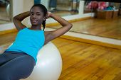 Portrait of fit woman exercising on fitness ball in fitness studio poster