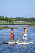 Man And Woman Stand Up Paddleboarding poster