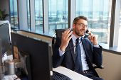 Businessman Making Phone Call Sitting At Desk In Office poster