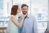 Affectionate woman kissing man in office poster