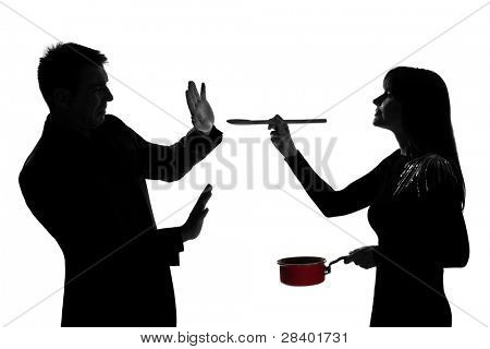 one caucasian couple man and woman tasting cooking sauce pan in studio silhouette isolated on white background