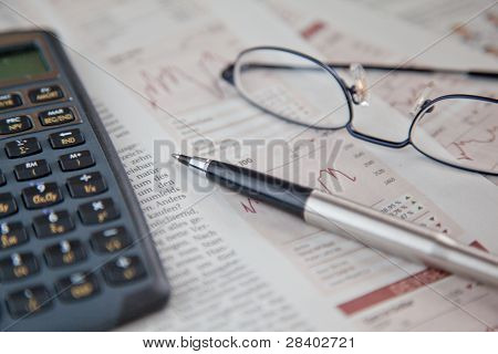 Ballpoint, Calculator And Reading Glasses On Newspaper Stock Chart