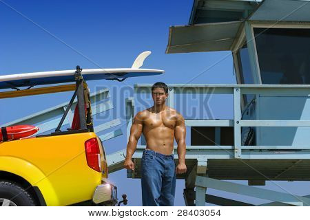 Hot hunky lifeguard on beach with truck and lifeguard stand