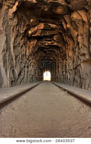 Light at the end of the tunnel. View inside a long railroad tunnel - bright light off in the distanc