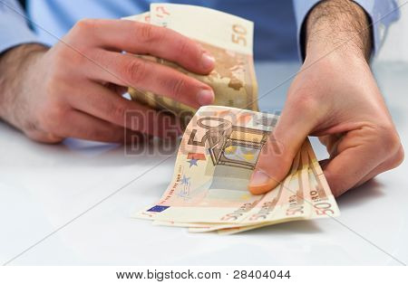 Man hands handling fan fifty euro money.