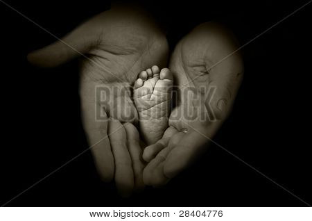 Babys foots in father hands on the monochrome background