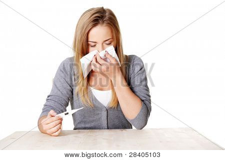 Young sick teenage woman checking her temperature