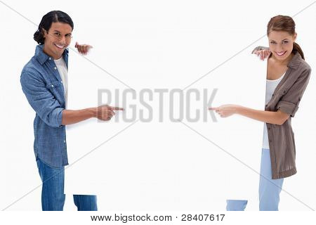 Smiling couple pointing at blank sign in their hands against a white background