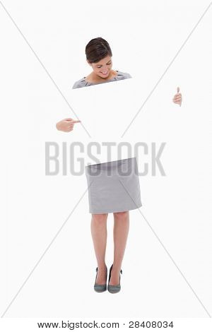 Woman pointing at blank sign in her hands against a white background