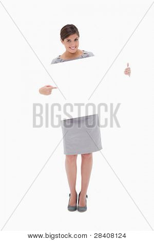 Smiling woman pointing at blank sign in her hands against a white background