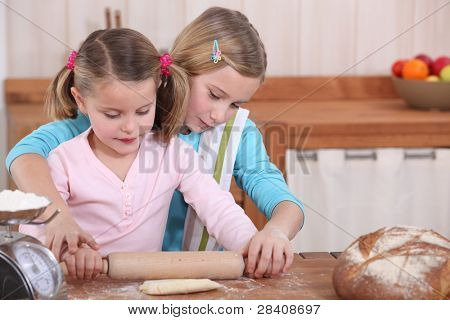 Sisters using rolling pin to roll dough