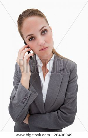 Bored looking bank employee on her cellphone against a white background