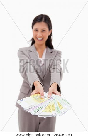 Money being offered by smiling businesswoman against a white background