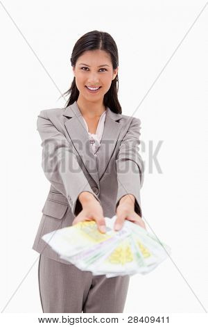 Smiling businesswoman offering money against a white background