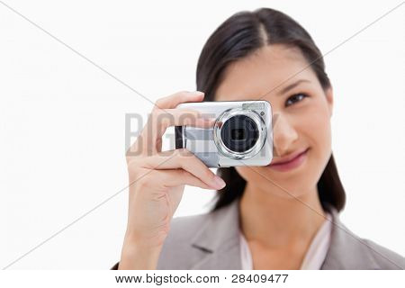 Businesswoman taking a picture against a white background