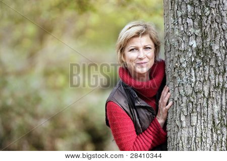 Timid woman hiding behind a tree