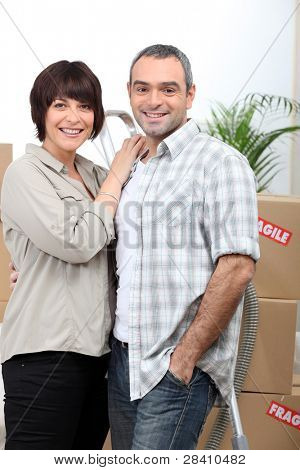 a couple behind  a pile of cartons inside a house