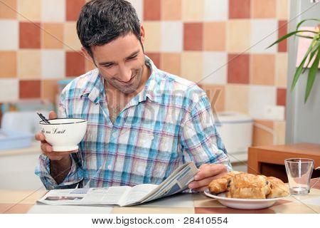 man einer Zeitschrift am Frühstückstisch