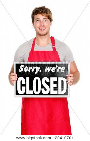 Business owner / employee showing closes sign. Man wearing red apron smiling happy. Caucasian male model.