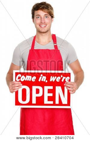 Business owner / employee showing open sign. Man wearing red apron smiling happy. Caucasian male model.