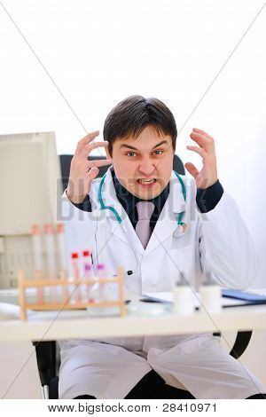 Stressed Medical Doctor Sitting At Office Table And Holding Hands Near Head