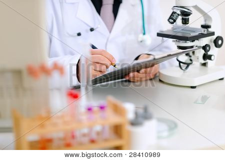 Medical Doctor Writing Something In Clipboard At Office Table. Close-up.