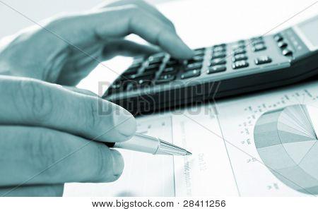 Closeup of businessman's hand doing paperwork - blue toned image