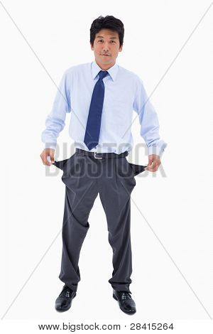 Portrait of a businessman showing his empty pockets against a white background