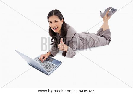 Lying woman with laptop giving thumb up against a white background