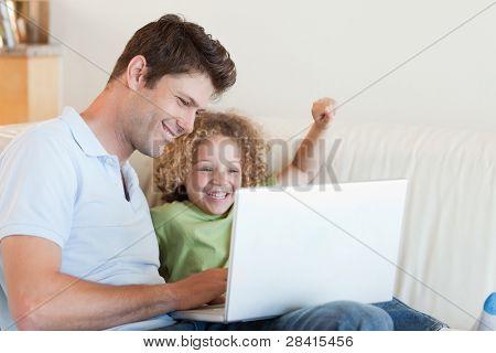 Muchacho alegre y su padre usando una laptop en su sala de estar