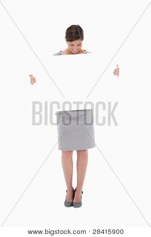 Woman looking down at blank sign in her hands against a white background