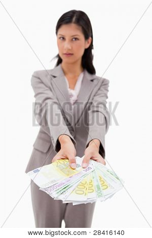 Money being offered by businesswoman against a white background
