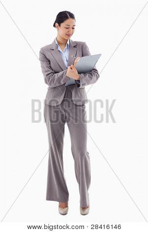 Portrait of a smiling businesswoman taking notes against a white background