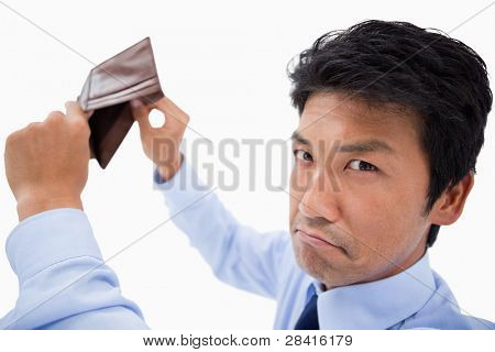 Broke businessman showing his empty wallet against a white background
