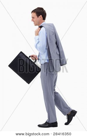 Side view of walking and smiling businessman with suitcase against a white background