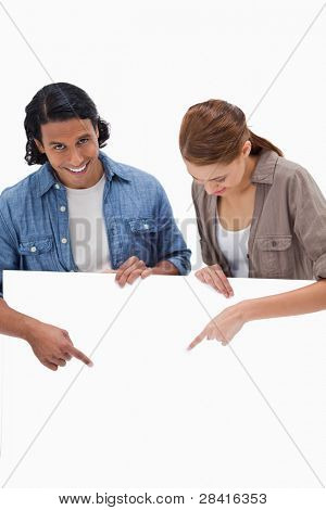 Smiling couple pointing down on blank wall against a white background