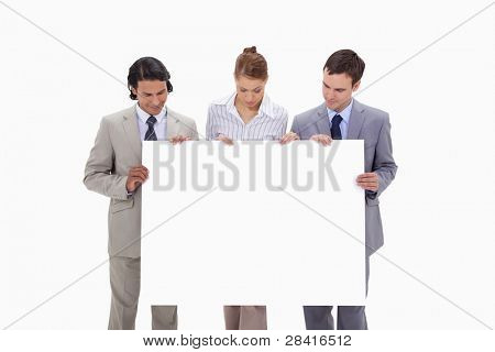 Businessteam looking at blank sign in their hands against a white background
