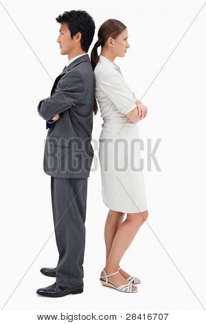 Portrait of serious business people standing back to back against a white background