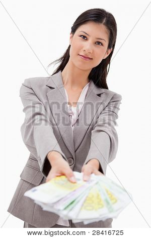 Businesswoman offering money against a white background