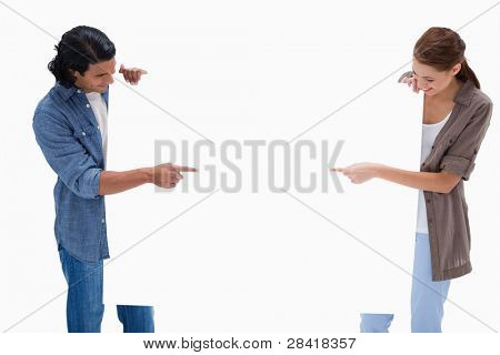 Couple looking and pointing at blank sign in their hands against a white background