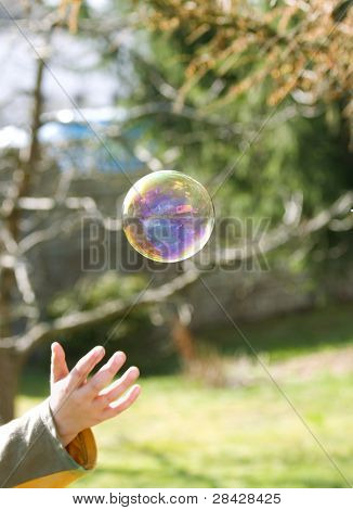Child hand and big soap bubble