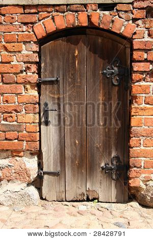 An old, rotten door in a brick wall
