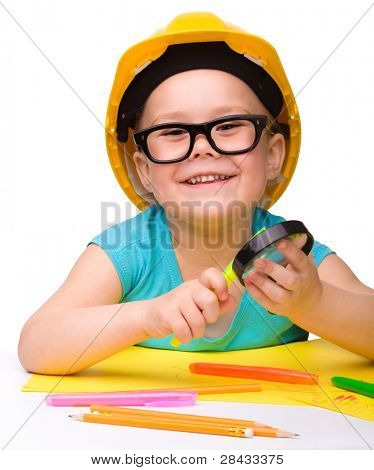 Cute little girl is playing while wearing hard hat, isolated over white